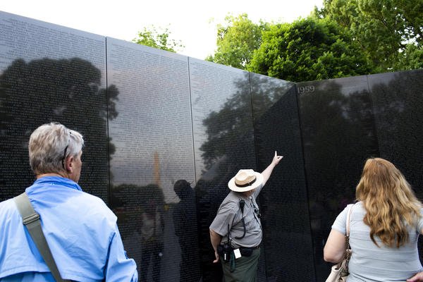 Robert Herendeen, National Park Service ranger, speaks to visitors at the Vietnam Veterans Memorial in Washington, D.C. Rangers like Herendeen have the task of collecting items left at the wall — including human remains.