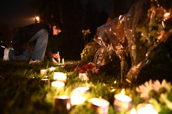 A woman kneels to place a candle outside the Tree of Life Synagogue after a shooting there left 11 people dead in the Squirrel Hill neighborhood of Pittsburgh.
