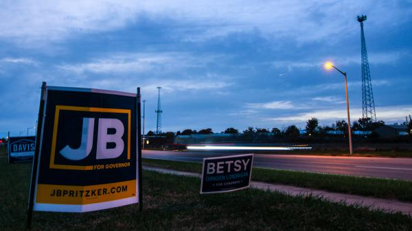 Cars pass a sign for gubernatorial candidate J.B. Pritzker about an hour before the polls closed on Nov. 6, 2018.