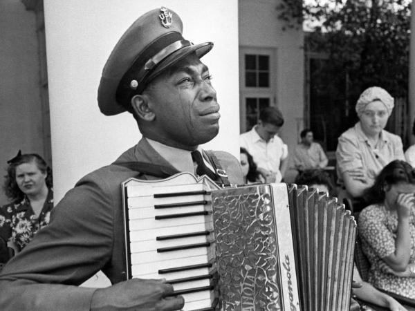 """U.S. Navy CPO Graham Jackson, with tears of grief, plays """"Goin' Home,"""" from Dvorak's 'New World' Symphony, as President Franklin D. Roosevelt's body is carried from Warm Springs, Ga., where he died."""