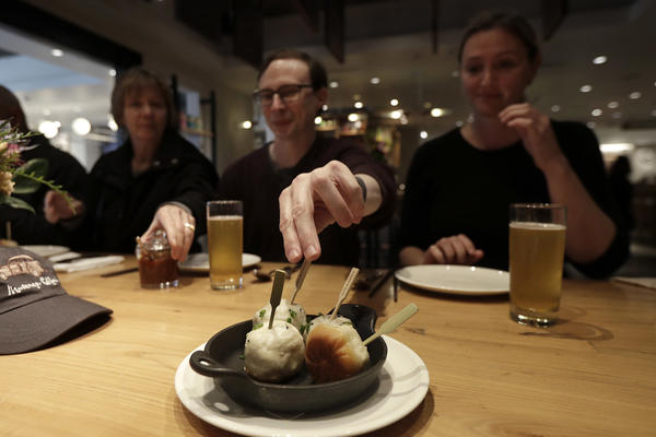 Mike Hardin, center, reaches for a dumpling while dining with others taking a tour with Avital Food Tours at China Live in San Francisco. (Jeff Chiu/AP)