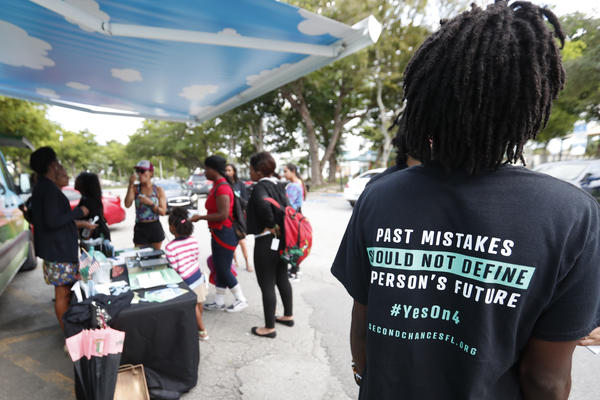 """People gather around the Ben & Jerry's """"Yes on 4"""" truck as they learn about Amendment 4 in Miami, which passed election day. Now, Gov.-Elect Ron DeSantis says he and state lawmakers will need to weigh-in before the amendment goes into effect, giving voting rights back to most felons in the state."""