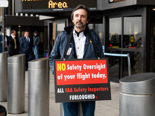 A man holds a placard at Newark Liberty International Airport on Tuesday, reminding travelers that FAA safety inspectors have been furloughed during the shutdown.