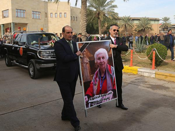Mourners transport the flag-draped coffin of Iraqi archaeologist Lamia al-Gailani, seen in the poster, for burial during her funeral procession in the National Museum in Baghdad on Jan. 21. Iraq is mourning the loss of a beloved archaeologist who helped rebuild her country's leading museum in the aftermath of the U.S. invasion in 2003.