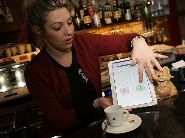 A waitress shows how to pay for a coffee with bitcoins.