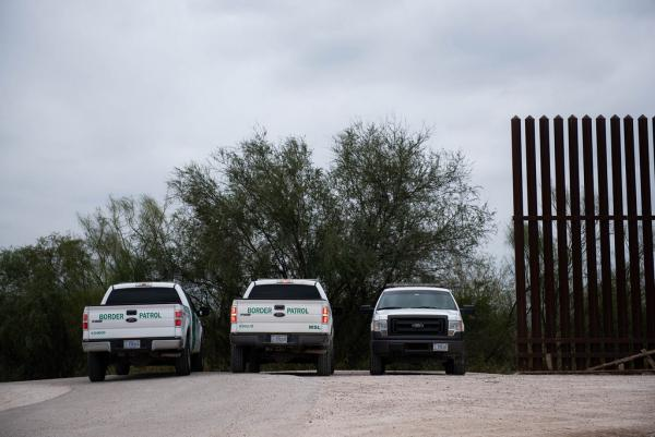 Border patrol trucks are parked next to a portion of the border wall in Hidago County.