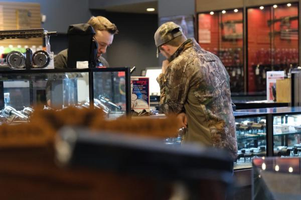 A customer shops at Frontier Justice, a gun store in Lee's Summit, MO. The number of documented background checks are high in 2018, but that doesn't necessarily mean gun sales are too.