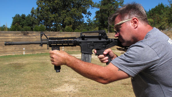 """Shooting instructor Frankie McRae aims an AR-15 rifle fitted with a """"bump stock"""" that allows the semi-automatic to shoot as fast as an illegal machine gun. As of March 26, bump stocks will be effectively illegal to own unless a court puts an injunction on the federal ban."""