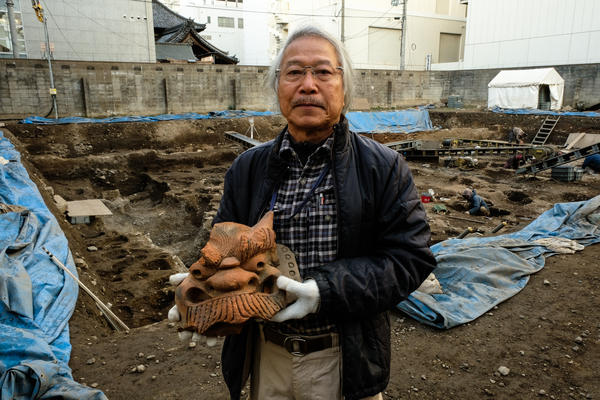Archaeologist Koji Iesaki holds a carved roof ornament excavated at the former site of the Jyokyo-ji temple in Kyoto, Japan. Iesaki and other archaeologists have their hands full as a pre-Olympic building boom has helped reveal centuries-old artifacts from the city's long history.