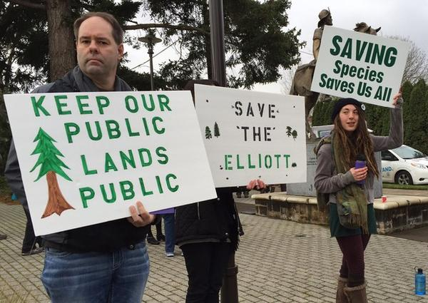 <p>Opponents of a plan to sell the Elliott State Forest hold signs outside an Oregon State Land Board meeting.</p>