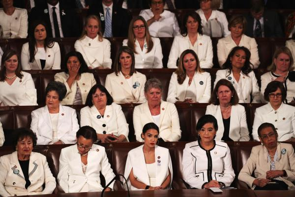 Female lawmakers dressed in white watch as Trump delivers the State of the Union address.
