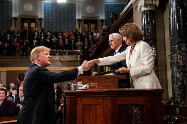 President Trump shakes hands with Speaker of the House Nancy Pelosi while joined by Vice President Mike Pence.