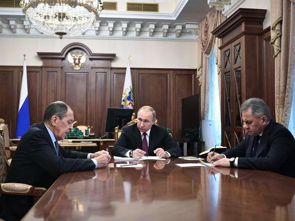 "Russian President Vladimir Putin (center) attends a meeting with Russian Foreign Minister Sergey Lavrov (left) and Defense Minister Sergei Shoigu in the Kremlin in Moscow on Saturday. Putin said Russia would abandon the 1987 Intermediate-Range Nuclear Forces treaty, calling it a ""symmetrical"" response to the U.S. decision to withdraw."