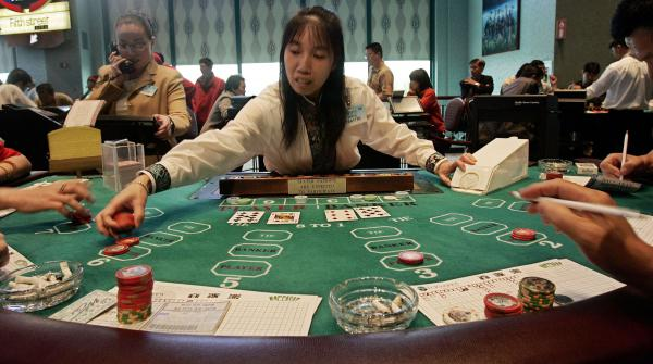 Dealer Cai Qilin, center, works on Mini Baccarat at an Asian gambling section in Foxwoods Resort Casino in Mashantucket, Conn., in 2006. Foxwoods estimated at the time that at least one-third of its 40,000 customers per day were Asian.