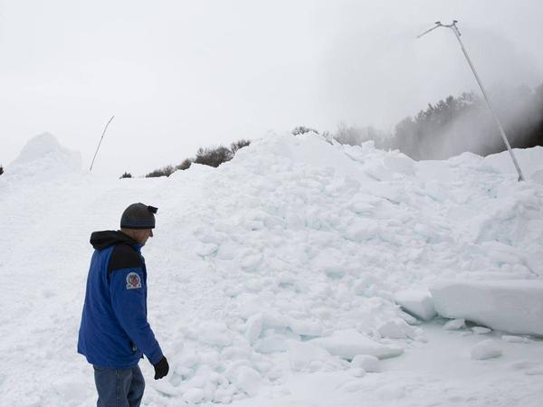 Volunteer Don Olson walks past a mound of artificial snow created by a snow gun on Tuesday at the Vasaloppet Nordic Ski Center in Mora, Minn.