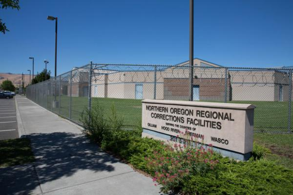 <p>NORCOR is a cinder block jail surrounded by a high chain-link fence and razor wire in an industrial section of The Dalles, Oregon.</p>
