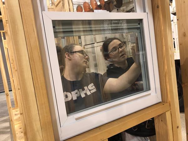 Oak Park junior Jasmine Bailey, right, shows a classmate in the Kansas City Construction Career Academy how to install a window.