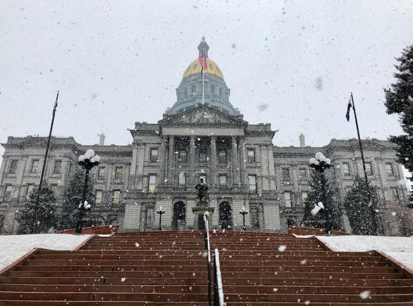 Snow falls at the State Capitol. Police have arrested a man suspected of damaging statues and glass display cases.