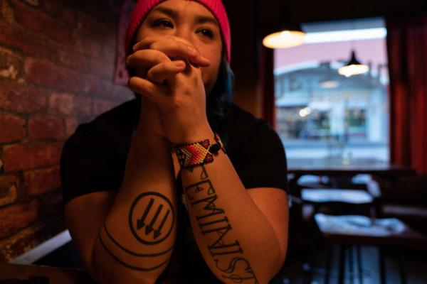 """<p>Rosie Strange sits in a restaurant after the Women's March on Jan. 19, 2019 in The Dalles, Ore. Her left arm says """"FEMINIST"""" and her right arm has an anti-fascist symbol on it.</p>"""