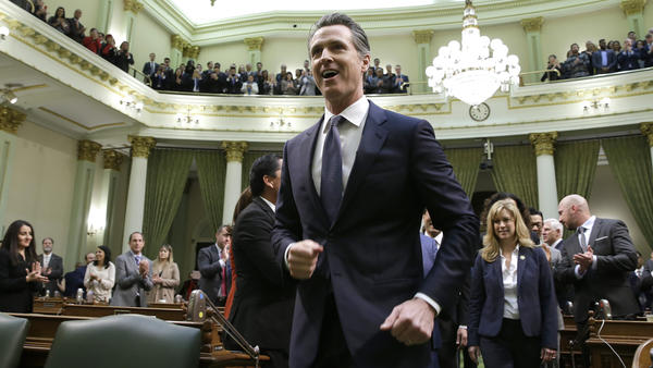 California Gov. Gavin Newsom walks up up the center aisle of the Assembly chambers to deliver his first of the State of the State Tuesday in Sacramento, Calif.