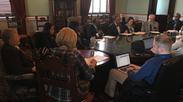 Senate Democrats sit around table talking to reporters