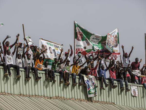 Supporters stand on a roof with placards and banners as they attend a campaign rally of the Nigerian opposition leader Atiku Abubakar on Thursday in Jimeta, eastern Nigeria.