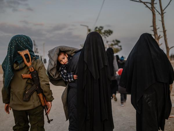 Veiled women reportedly associated with ISIS walk under the supervision of a female fighter from the Syrian Democratic Forces in northeastern Syria on Sunday. Over the weekend, President Trump demanded European allies repatriate their citizens captured as ISIS fighters.