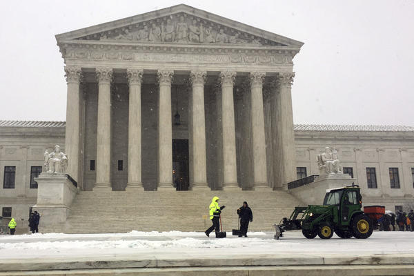 Crews remove early morning snow during a winter storm at the Supreme Court on Wednesday. It's not unusual for the high court to be open when the rest of Washington is closed.