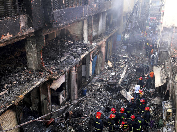 Locals and firefighters gather around buildings that caught fire late Wednesday in Dhaka, Bangladesh, on Thursday, killing dozens of people.