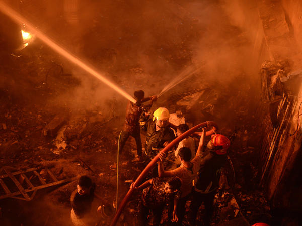 Firefighters try to douse flames after the devastating fire that raced through at least five buildings in an old part of Bangladesh's capital.