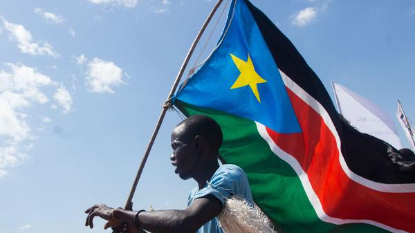 A man carries South Sudan's national flag at Mangateen Internal Displaced persons center in Juba on November 17, 2018. Sudan's civil war has led to the displacement of millions of people.