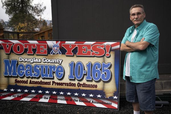 Tom McKirgan stands in front of his house in Camas Valley, Oregon, with a campaign sign supporting the Douglas County Second Amendment Preservation Ordinance. McKirgan, a member of the Oregon chapter of the Three Percenters militia group, helped draft the Douglas County ordinance.