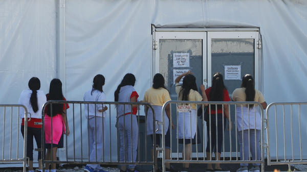 Children line up to enter a tent at the Homestead Temporary Shelter for Unaccompanied Children. Once youth turn 18, they are aged out of the children's shelter and are at risk of being placed in an adult detention facility.