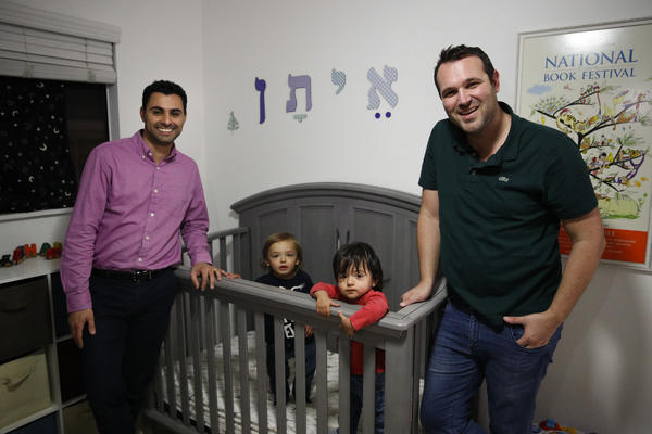 Elad Dvash-Banks (left) and his husband, Andrew, pose for photos with their twin sons, Ethan (center right), and Aiden in their apartment last year in Los Angeles.