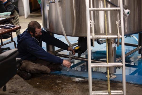 Brewer Brian Cox works on a tank at the Hanging Hills Brewing Company in Hartford.