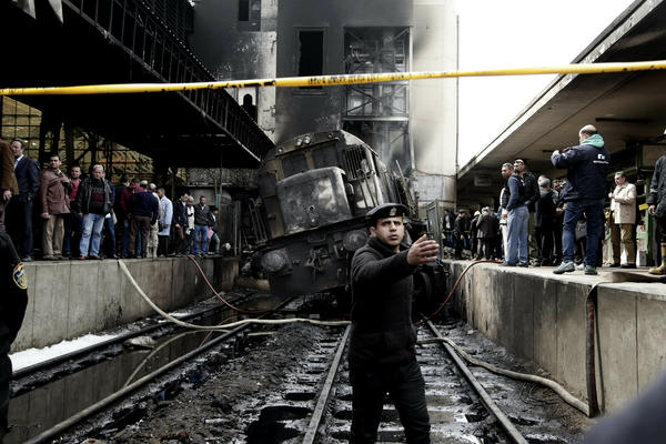 Policemen stand guard in front of a damaged train inside Ramses train station in Cairo, Egypt, on Wednesday.