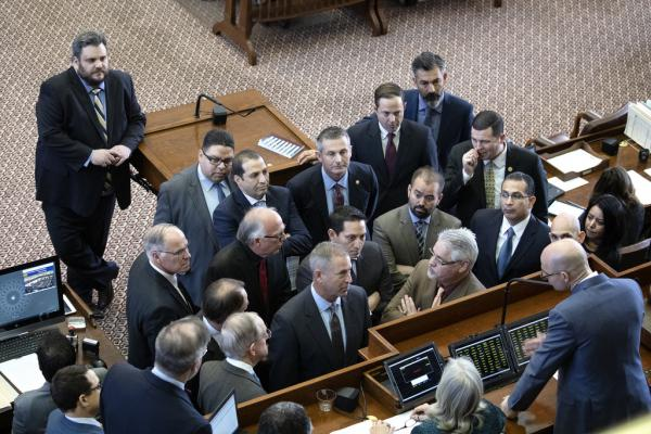Texas representatives huddle around the dias on the second day of the 86th legislative session.