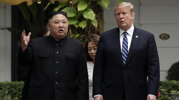 President Trump and North Korean leader Kim Jong Un take a walk during their meeting in Hanoi, Vietnam, on Thursday.