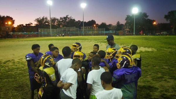 Mo Better Jaguars' coaches and players huddle at the end of practice at Betsy Head Park in Brownsville, Brooklyn in September 2014.