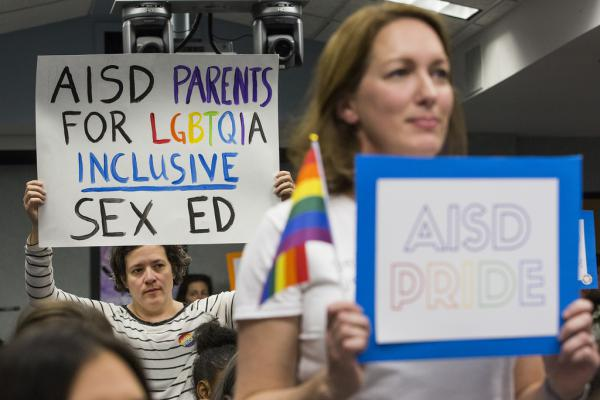 Erika Bodoin (left) and other community members hold signs in support of adopting National Sexual Education Standards during an AISD board meeting on Monday.