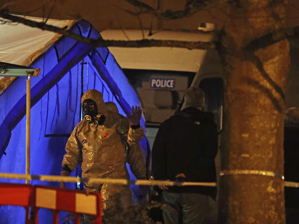 Investigators walk next to a police tent last year in Salisbury, England, near where former Russian double agent Sergei Skripal and his daughter Yulia were found critically ill.