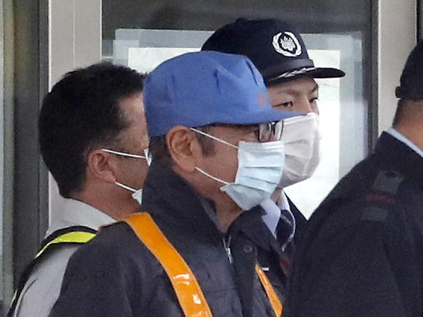 A man in a blue cap and mask is believed to be former Nissan Chairman Carlos Ghosn as he leaves a Tokyo jail surrounded by security guards.
