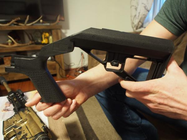 Gabriel Hodge holds up a bump stock, a plastic attachment that turns a semi-automatic rifle into a virtual machine gun. Bump stock owners, like Hodge, are in limbo after the ATF ruled the devices are illegal, a decision that has been challenged in court.