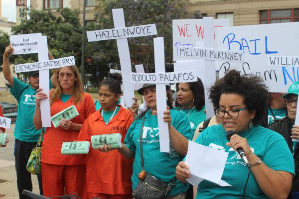 Protestors with Texas Organizing Project dress as inmates and hold crosses bearing the names of people who they say have died in custody during pre-trial waiting periods.