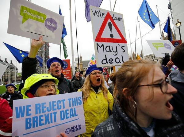 Anti-Brexit activists hold placards and wave flags as they demonstrate outside the Houses of Parliament in London on Tuesday, ahead of a crucial vote on Prime Minister Theresa May's Brexit deal.