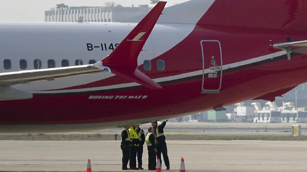 Members of the ground crew chat near a Boeing 737 Max 8 plane operated by Shanghai Airlines and parked on the tarmac at Shanghai Hongqiao International Airport in China. On Monday, the Civil Aviation Administration of China ordered all the country's airlines to ground their Boeing 737 Max 8 planes after Sunday's fatal crash of the same model plane in Ethiopia.