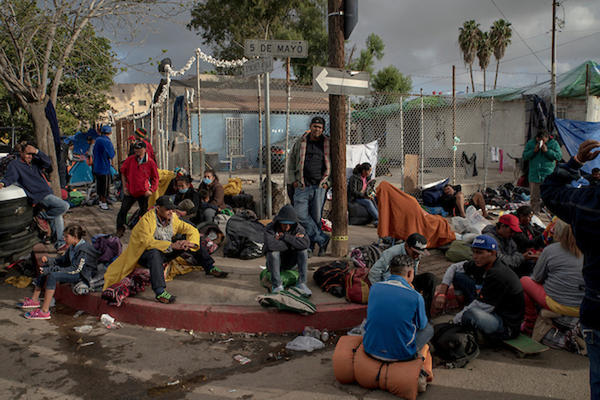 A group of migrants sit outside the Benito Juarez sports complex where they have taken temporary shelter in Tijuana, Mexico on November 30, 2018. (Kitra Cahana)