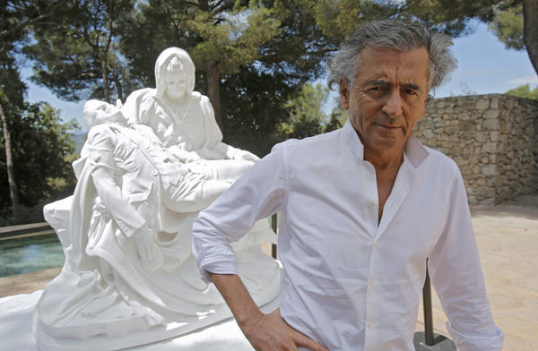 """French philosopher Bernard-Henri Lévy poses close to sculpture """"Merciful Dream"""" by Jan Fabre during the preparations of the """"Adventures of truth"""" exhibition in Saint Paul de Vence, France, on June 25, 2013. (Lionel Cironneau/AP)"""