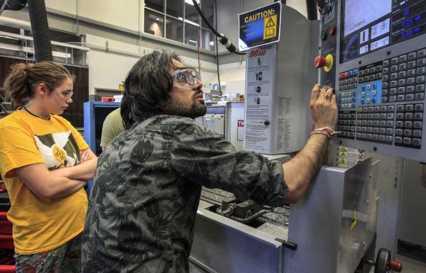 Wichita State teaching assistant Pavan Bhavsar works with students at the College of Engineering's Mechanical engineering department.