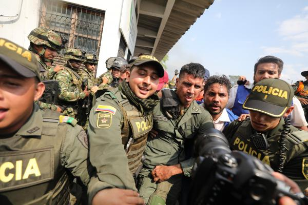 Colombian police escort a Venezuelan soldier into Cúcuta, Colombia. The soldier surrendered at a bridge crossing the Venezuela-Colombia border, where people tried to carry humanitarian aid into Venezuela on Feb. 23.